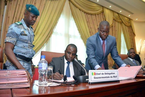 Col. Moussa Sinko Coulibaly, center, a Malian government minister, signs a peace agreement with Tuareg rebels Tuesday at a meeting in Ouagadougou, Bukino Faso.