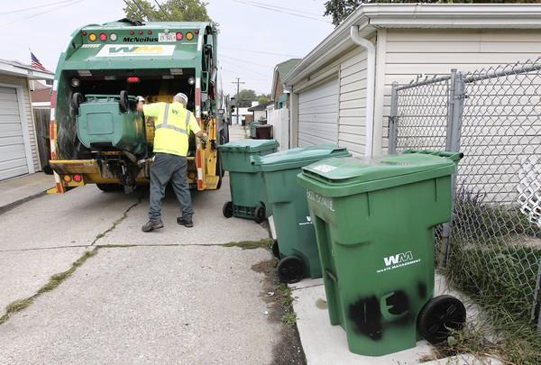 An employee for Waste Management collects trash in Berwyn in 2011. Orland Park recently signed off on a 10-year contract with the Houston-based company.