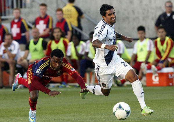 Real Salt Lake forward Robbie Findley, left, loses his footing as he and Galaxy defender A.J. DeLaGarza (20) chase down the ball during the first half of a game on June 8.
