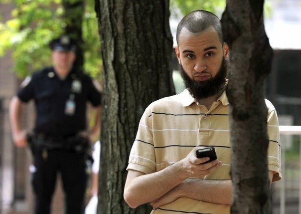 An NYPD officer and a man look on as civil rights and legal advocates and residents hold a news conference in New York outside One Police Plaza to discuss planned legal action challenging the department's surveillance of businesses frequented by Muslim residents and area mosques.