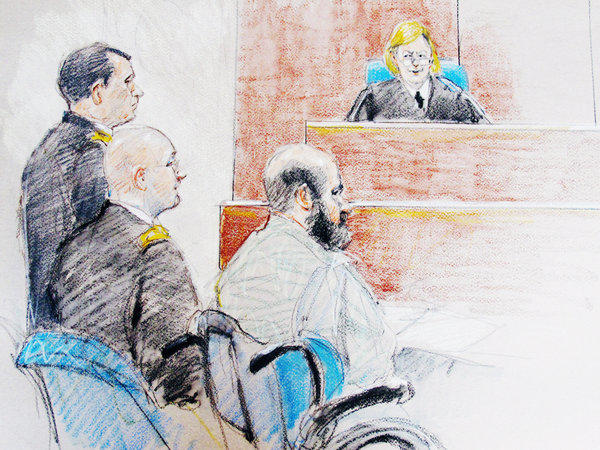 In this file courtroom sketch, Nidal Malik Hasan, right, is seen sitting by his former defense attorneys during a hearing at Fort Hood, Texas. The judge, Col. Tara Osborn, has said the long-delayed trial into the mass shooting at the base will begin next month.