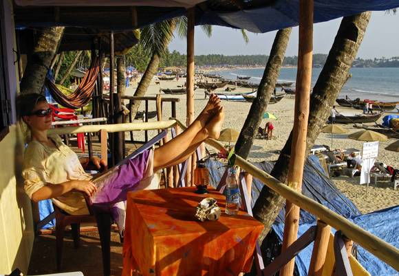 Tourist woman enjoys the view from the balkony of her beachhut on the fine sandy beach Palolem in Goa , India.
