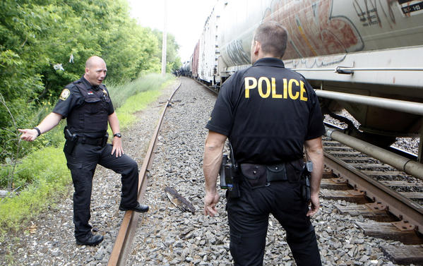 Special Agent Matt Johnson, with the Norfolk Southern Police Department, left, stands along the railroad right-of-way Tuesday in South Bend speaking with Mishawaka Police Cpl. Ryan Corbett as the railroad conducts a campaign locally about railroad track safety and trespass laws.