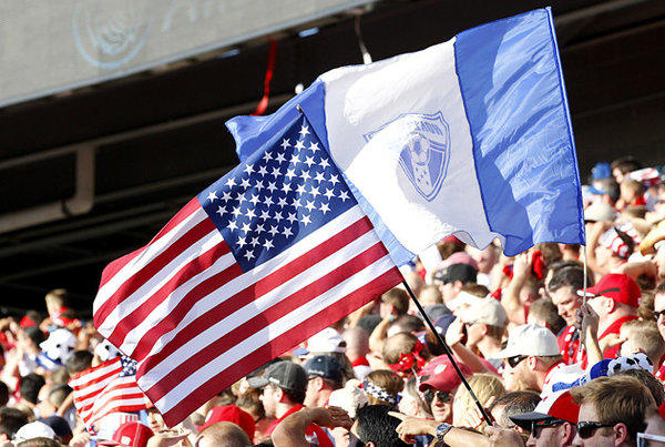 Fans of the United States and Honduras fly flags from each country during the first half of the World Cup qualifying match.