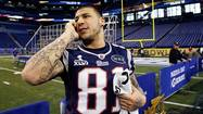 Patriots tight end Aaron Hernandez talks on a phone during media day for the NFL Super Bowl XLVI in Indianapolis
