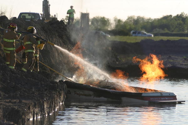 Firefighters douse the flames on a boat owned by the Aberdeen Aqua Addicts water ski team during a fire Tuesday on Dahme Lake near Aberdeen.