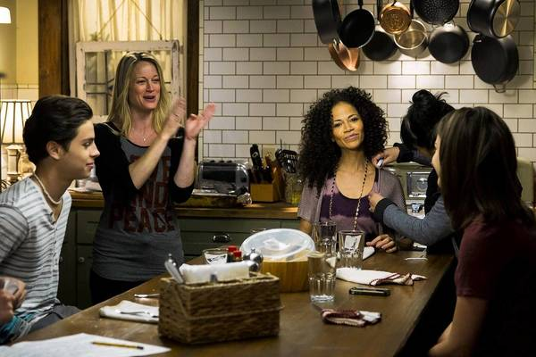 "Teri Polo, standing, and Sherri Saum (seated at center) star in ""The Fosters."""