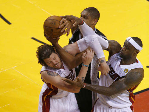 San Antonio Spurs power forward Tim Duncan (21) battles for a rebound with Miami Heat small forward LeBron James (6) and Mike Miller (13) during the third quarter of game six in the 2013 NBA Finals at American Airlines Arena.