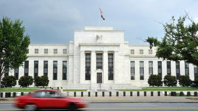 Fed holds steady on interest rates and stimulus, sees risks easing
