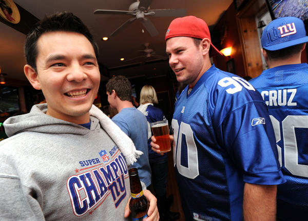 New York Giants fans Max Hill (left) and Mark Brier share a laugh at the Americana. The Americana, which will close in July, was a bar for Giants fans.