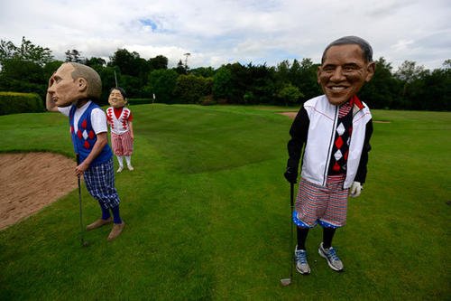 Oxfam activists depicting Russia's President Vladimir Putin (L), Japan's Prime Minister Shinzo Abe and U.S. President Barack Obama take part in a media event to highlight world hunger during the G8 summit, at Enniskillen Golf Course in Enniskillen, Northern Ireland June 18, 2013.
