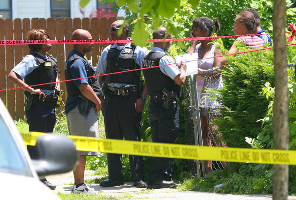 Chicago police investigate a shooting in the 10900 block of South Perry Avenue today as a family member of victim waits for news of the victim's condition.