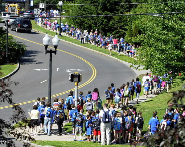 A parade of students from the Morley School in West Hartford snakes its way from the school to town hall to deliver backpacks and school supplies to the town's social service agency. The packs and supplies will be handed out to children in need. Three hundred thirty-four students with 433 packs forming the Backpack Brigade made the mile long walk Wednesday morning with an escort of police and the fire department.