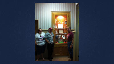 Taija Daniels, Jackie Lewis and the Rev. William Dodson show the displayed arts and crafts done by the center's youth.