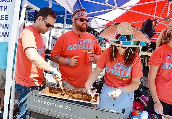 Angelo Barriga, left, Nick Fisher and Roya Waltman of Chili Royale stir and serve chili to raise awareness for their nonprofit basketball league at Edison High School at the sixth annual Chili at the Beach event in Downtown Huntington Beach on Saturday.