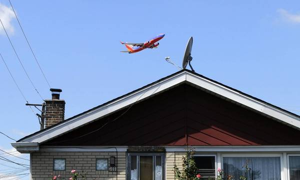 A low-flying plane lifts off over a house near Midway International Airport. Proximity to high traffic zones, in the skies and on the ground, is a key consideration when buying a home.