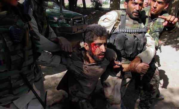 Afghan security forces detain a suspected Taliban fighter injured in a clash with police in Nangarhar province. The fighting came a day before the U.S. and the Taliban were to begin direct talks.