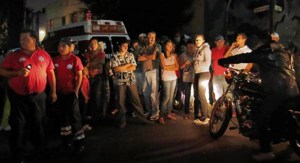 Residents and emergency workers gather at the scene of a shooting in Mexico City's Tepito neighborhood. The mayor has deployed additional police to Tepito, home to 12 people who went missing from a bar in the capital in May.
