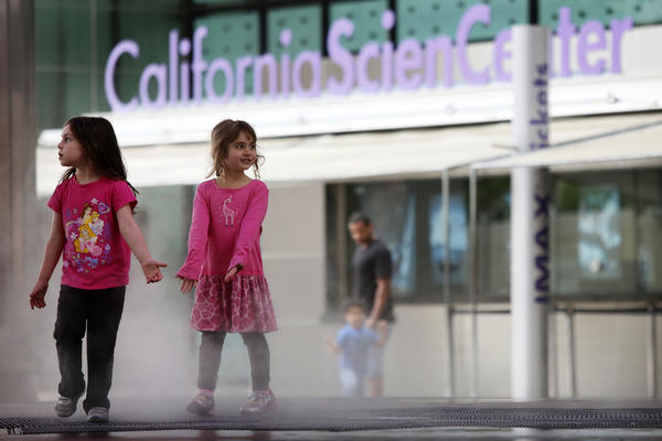 Two girls play in the mist from a fountain at the California Science Center.