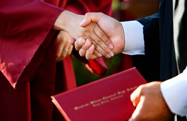 Gonzalo Moraga, right, principal of instruction at Woodrow Wilson Classical High School in Long Beach, shakes hands with a graduate during the school's commencement ceremony. Moraga said that he shook hands with over 400 students during the ceremony.
