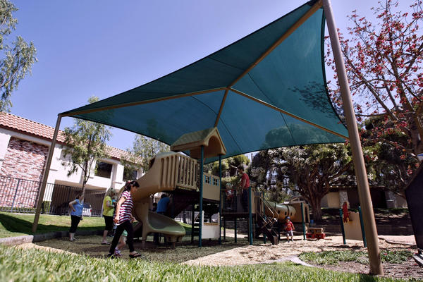 Children play under the shade at the playground in Memorial Park in La Canada Flintridge on Tuesday, June 18, 2013. The city recently installed the large cover to provide protection from the elements of nature.