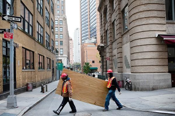 Workers in New York carry boards to cover subway air vents as Superstorm Sandy approached in October.