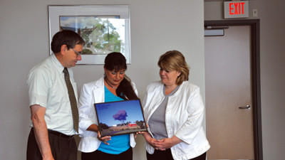 "Indian Lake Borough resident Val McClatchey, center, donates a copy of her photo ""End of Serenity"" to Somerset County Commissioners John Vatavuk and Pamela Tokar-Ickes. The photo will be added to the Flight 93 museum aboard the USS Somerset."