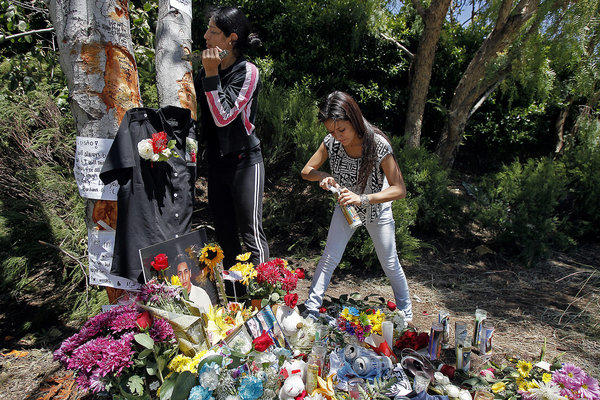 Bernice Torres, left, carves a heart in a tree Monday as Nicole Balbuena, right, lights a candle at a memorial where Luis Adrian Torres died in a car crash on Sunday.