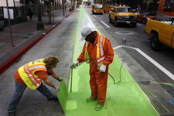 Darryl Strucke and Alvin Pegues, both painters with the L.A. Department of Transportation, create a bike lane along Spring Street in downtown Los Angeles.