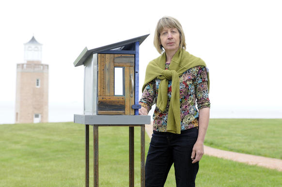 "Visual attist and ecological designer Ana Flores of Charlestown, R.I., stands by her work titled ""Sigue Caminando/ Keep Walking."" Flores is the organizer of ""Poetry of the Wild: Avery Point,"" a beach walk on the University of Connecticut satellite campus in Groton displaying ""poetry boxes,"" little kiosks designed by local artist"