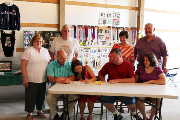 Erica Westbrook of Boyne Falls (middle) recently signed at Kirtland Community College where shell be a member of the womens cross country team. Family members, friends and KCC cross country coach Don Haskin (seated, left) look on.