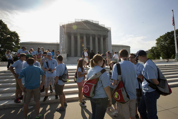 Visitors wait outside of the Supreme Court in anticipation of key decisions.