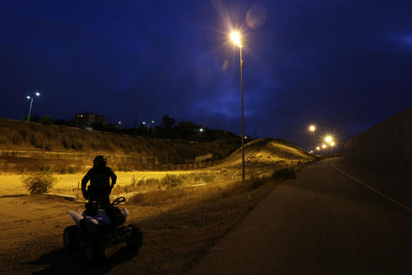 A U.S. Border Patrol agent rides an ATV as he patrols between the border structures separating Tijuana, Mexico, left, from San Diego.