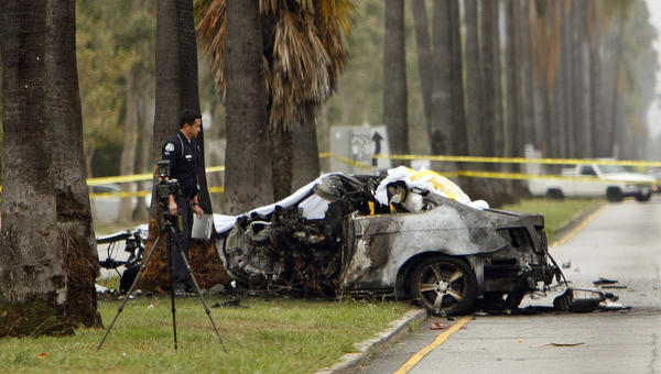An LAPD officer investigates the scene of a single-vehicle accident in which journalist Michael Hastings was killed when his vehicle crashed into a tree and caught fire in Hancock Park.