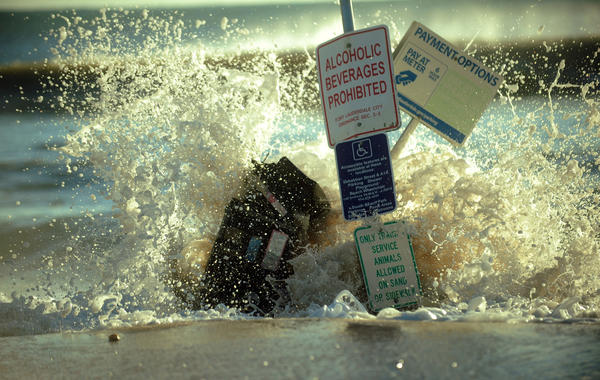 Waves crash over a parking meter machine and beach signage on A1A that is covered with sand from Hurricane Sandy at Ft. Lauderdale Beach, Florida.