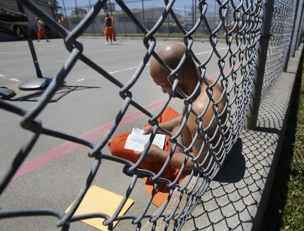 Inmate Curtis Colvard Sr. reads a Bible in the exercise yard of Sacramento County's Rio Cosumnes Correctional Center in Elk Grove. Federal judges ordered Gov. Jerry Brown Thursday to immediately begin releasing inmates from the state's crowded prisons.