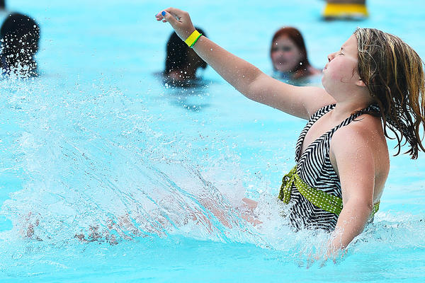 Haylee Stottlemyer, 10, of Hagerstown, makes a splash off the water slide at Claude M. Potterfield Pool Thursday during an outing with the Girls Inc. summer camp in Hagerstown.