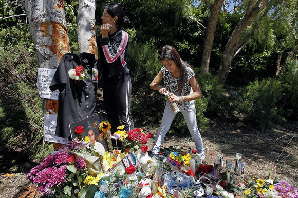 Relatives of a 19-year-old Costa Mesa man construct a memorial where his car hit a tree Sunday morning. The memorial was later removed after a neighbor complained.