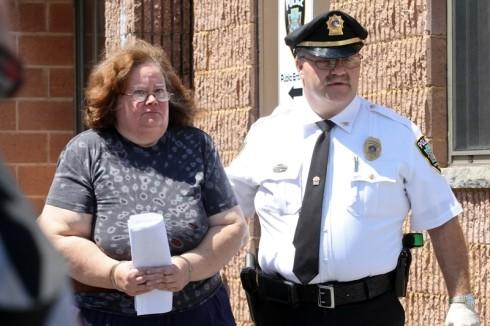 Susan Gensiak is escorted from Taylor police headquarters Wednesday morning.