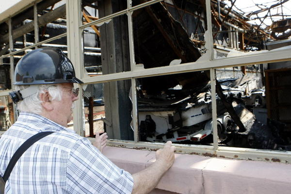 South Bend Tribune/GREG SWIERCZ John Cocquyt, owner, looks into the burned wreckage of the former RMG Foundry building in Mishawaka today.