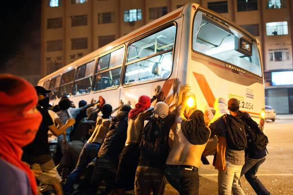 Demonstrators in Niteroi, near Rio de Janeiro, overturn a bus during protests. Clashes with police continued even as bus fare hikes were rolled back in two cities after protests.