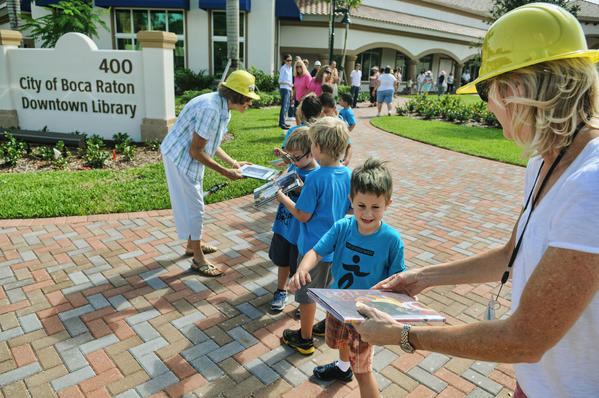 fl-boca-book-brigade-1: Boca Raton Library Assistant 2 (right) Kim Sexton hands a book to kids from Camp Boca as they pass books from the old Boca Raton Library to the new City of Boca Raton Library a block away Thursday morning in Boca Raton. The book will be closed on the old Downtown Library so a new will be opened. The last 100 books from the old library were moved person-to-person to the new. It's an event that was $9.5 million in the making. Photos by Taimy Alvarez, Sun SentinelBi