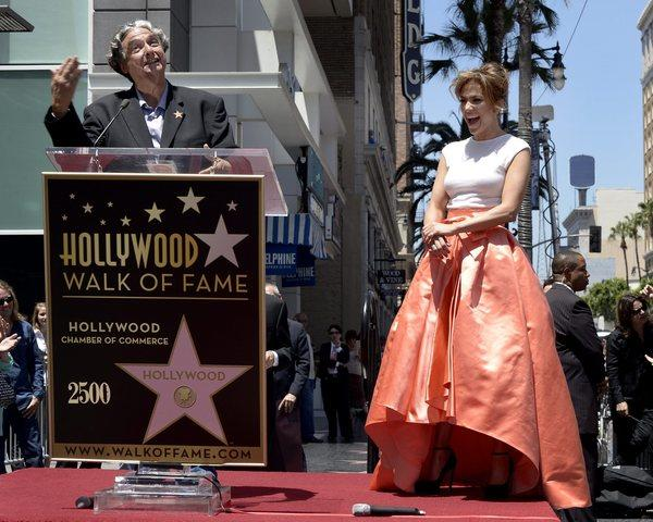 Jennifer Lopez laughs as director Gregory Nava holds forth during Lopez's star ceremony on the Hollywood Walk of Fame on Thursday.