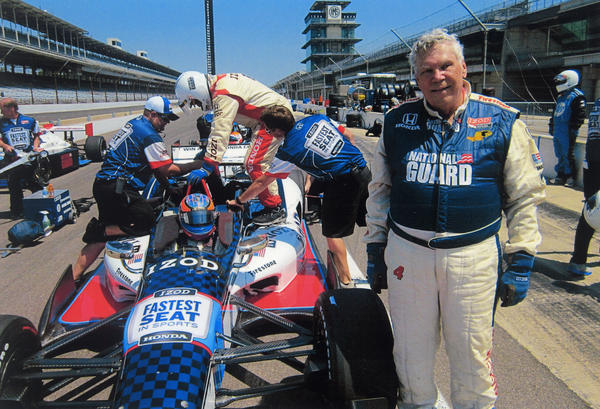 Harold Lowe poses in front of an Indy Car just after completing three laps at 180 miles per hour.
