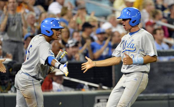 UCLA's Christoph Bono, right, is congratulated by teammate Kevin Williams after scoring the go-ahead run in a win over LSU on Sunday. The Bruins are beating opponents despite their less-than-stellar team batting average.