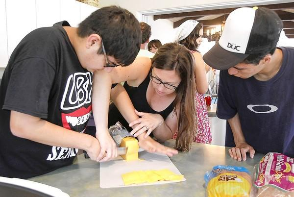 Instructional assistant Dana Rice prepares grilled cheese sandwiches with vocational education students Andrew Arredondo, left, and Tyler Fisher, right, during a recent class at the Assistance League's kitchen in Laguna Beach.
