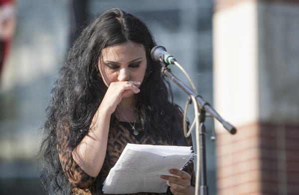 Taym Alhusseini, a Mishawaka High School student and refugee of Iraq, tells her story on stage during World Refugee Day on Thursday on the gridiron at the former College Football Hall of Fame in South Bend.