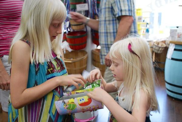 Sisters Carly Wilson, 8, and Summer, 4, check out a box of goodies they received at Balboa Candy in Newport Beach on Thursday. The two placed in their respective age groups during the annual Newport-Mesa Spirit Run in March and received a gift certificate to the Balboa Peninsula candy store.