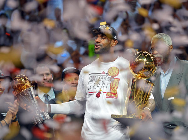 LeBron James holds the MVP trophy and the Larry O'Brien Championship trophy after defeating the Spurs in Game 7.