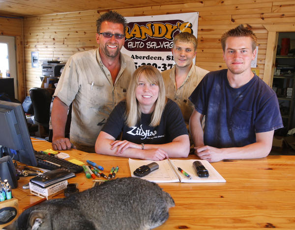 The staff at Randy's Auto Salvage from the left are: Randy Scherbenske, Brittany Scherbenske, Jack Evelo and Cade Scherbenske. In the foreground is Mama Kitty.